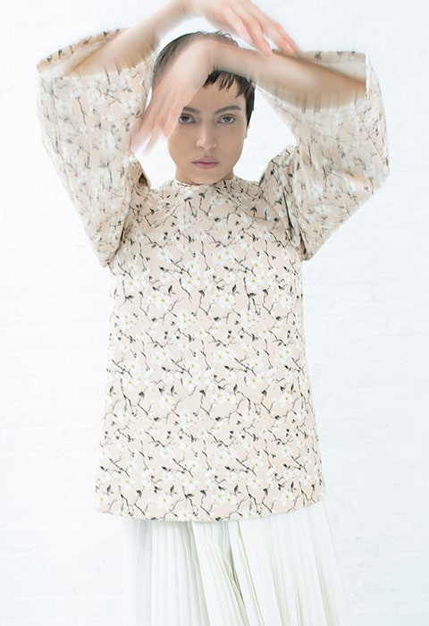 Upper body shot of a nude and black short floral tunic, ivory pleated skirt with additional pleated panel