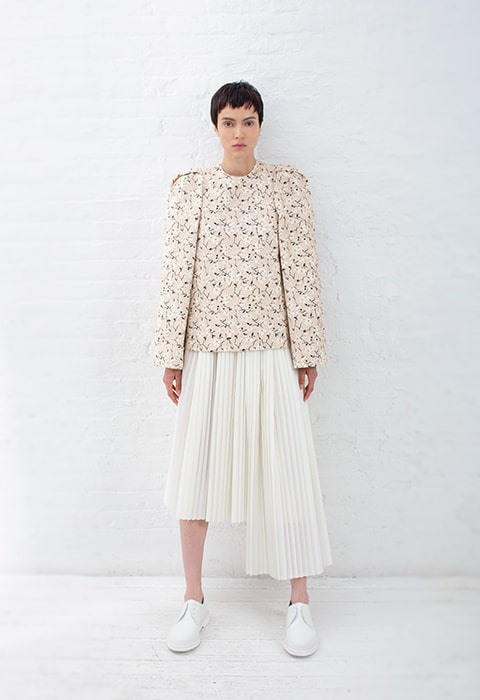 Full body shot of a nude and black short floral tunic, ivory pleated skirt with additional pleated panel